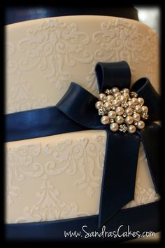 Navy Blue wedding cake Close up of detail with pretty broach
