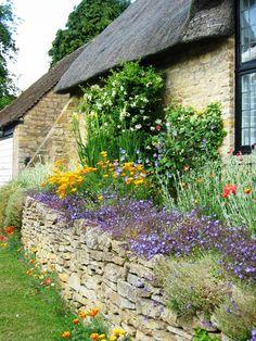 Engelse cottage met stenen muurtje en bloemen. #garden #flowers