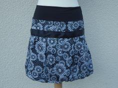 De face  Jolie jupe boule en coton noir avec des fleurs grise. Un ruban en satin noir de 4 cm est cousu sur le devant et se noue dans le dos. La ceinture de cette jupe est en lycra (jersey ou tissu extensible suivant disponibilité en magasin) pour s'adapter à toutes les morphologies.