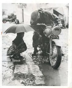1943- Little Italian girl watches as a British dispatch rider works to get the water out of the carburator of his motorcycle.