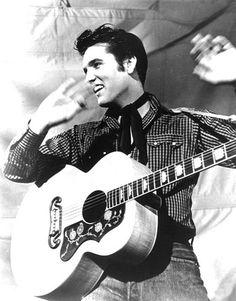 ELVIS PRESLEY avec sa Gibson Jumbo  -  Il s'agit d'une photo du King Elvis PRESLEY mise en ligne, par Ritchie CLIFFORD, à l'occasion du 33ème anniversaire de sa disparition. Il tient en bandoulière sa fameuse guitare Gibson JUMBO