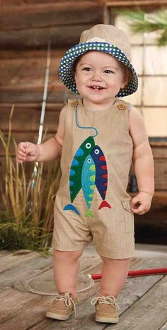 A baby boys brown cotton romper is perfect for a warm summer's day. This adorable fishing romper for newborn and infant boys is adorable with embroidered detail, trio of colorful fish and side cargo pockets. Inner leg snaps. This baby boys fishing outfit is just too cute!