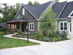 A clean and simple hardscape, plus a traditional lawn and a harmonious planting bed, allows the lines of the house itself to stand out. The lamppost fits the style of the house and serves as an accent piece. Providing a patch of light to mark the start of the path at night isn't a bad idea, either.