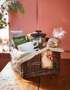 Ein Geschenkkorb mit einer Packung Kaffee, einem Kaffeezubereiter, Bechern und Haferkeksen