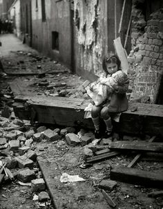 The Blitz, London, 1940: Baby girl hugs her doll sitting outside her home demolished by a German bomb. Her surroundings are very dangerous -- walls ready to collapse, loose masonry, metal fragments -- but that did not stop the photographer from snapping the picture.