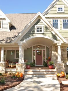 Custom Home - Door County, WI  This home exterior has Cedar Shake siding in Sherwin Williams 2851 Sage Green Light stain color with cedar trim and natural stone accents. The windows are Coconut Cream colored Marvin Windows, accented by simulated divided light grills.Custom Home - Door County, WI