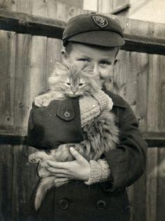 Good tempered kitten being hugged by school boy in 1953.
