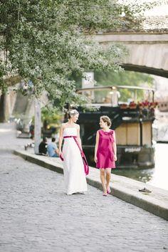 noni 2014 carlotta, brautkleid mit pinken akzenten und passendem trauzeuginnenkleid in pink, beide mit großer pinker schleife (Foto: Le Hai Linh) (http://www.noni-mode.de)