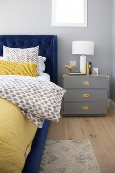 Britany Simon Design Arcadia Residence Transitional bedroom with stunning royal blue upholstered bed, neutral gray walls, gold and yellow accents.
