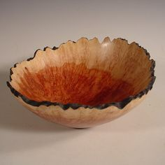 Nelsonwood's hand turned burl bowls emphasize flaws that have been caused by insects or deformities. These rustic imperfections contrast with the smooth finish Bryan gives to the rest of the surface.