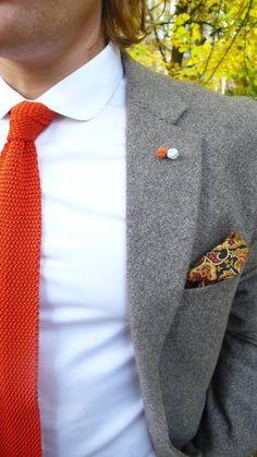 Knitted orange/grey lapel pin ball thingies.