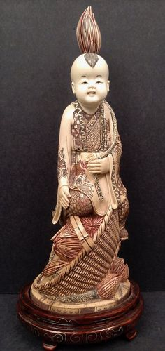 A MAMMOTH IVORY CARVING OF A BOY FIGURE WITH LOTUS FLOWER