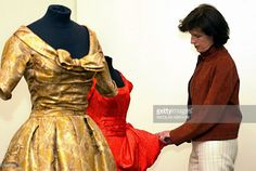 Princess Esmeralda of Belgium arranges an Yves Saint Laurent for Christian Dior dress spring-summer 1958 (expected to fetch 5,900-8,800 Euro) and a Christian Dior woven and printed gold silk dress autumn-winter 1957 (expected to fetch 2,950-4,400) who was worn by her mother Princess Lilian of Belgium at Sotheby's in London 14 May 2003. Preview of jewels and couture from the collection of the late HRH Princess Lilian of Belgium ahead of its sale next week. Considered as the greatest and…