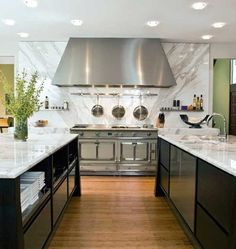 Stone Slab backsplash i this pretty kitchen with stainless, write and gray marble, and black cabinets