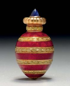 A Small Two-Color Gold Mounted Guilloché Enamel Egg-Shaped Scent Bottle By Fabergé, workmaster's mark of Michael Perchin, St. Petersburg, circa 1890, scratched inventory number 7594 The egg-shaped body horizontally decorated with gold laurel bands and red enamel over a guilloché ground, the lobed gold cover with cabochon sapphire finial, enclosing a gold stopper, marked on inner rim 1¼ in. (3.2 cm.)