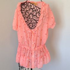 Pink sheer blouse with detail. Button up blouse with scoop neckline, ruffle and gathered at seams front and back. Gathered at arm openings and neckline. Tie at front. Sheer. Nice layering piece in very good used condition. Wrangler Tops Blouses