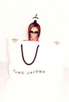 Victoria Beckham para primavera verano 2008. Solo usando un collar rosa y bolsa de plastico, saliendo de una enorme caja de #zapatos