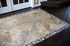 Love this custom tile inset on the dark hardwood floors in the entryway.  Great alternative to a rug!    http://flahertysflooring.com