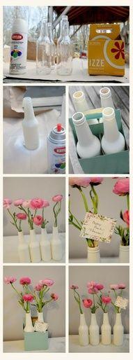 Faça você mesma os seus vasos! Pinte garrafas de refrigerante com spray branco e as decore com flores naturais ou artificiais.
