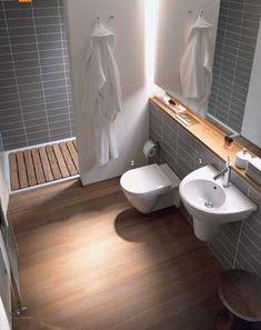 Pour optimiser l'espace dans une petite salle de bain, miser sur un carrelage gris en mural avec une peinture blanche et un parquet en teck pour un résultat déco au top