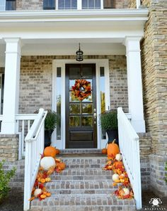 traditional-fall-front-porch-on-brick-and-stone-home-with-pumpkins-and-leaves-cascading-down-stairs
