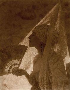 Baron Adolphe de MEYER (1868-1946) <br  /> Tortola, Valence, 1918 <br  /> Épreuve d'époque au platine montée sur support cartonné. Encadrée. <br  /> 24,3 x 19,4 cm. (9 5/8 x 7 5/8 in.) <br  /> Quelques retouches d'époque au niveau du visage et des boucles d'oreilles. <br  /> Provenance : archives Conde Nast. <br  />  <br  />  <br  />  <br  />