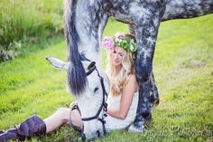 Horse photography session: blonde girl wearing a flower crown and white dress, sitting on the ground in front of her grey gelding.