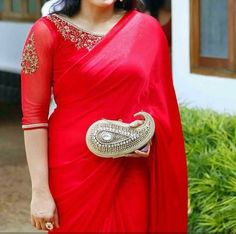 Pretty simple red saree and statement blouse. Love the statement paisley shaped clutch! 3/4 saree blouse. Indian fashion.