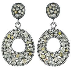 A Pair of Colored Diamond Ear Pendants. Each suspending a vari-cut colored diamond plaque, within a pavé-set diamond surround and inner ring, from a pavé-set diamond circular link, to the vari-cut colored diamond cluster surmount, mounted in 18K blackened gold, length 2 1/4 inches. Via Phillips.