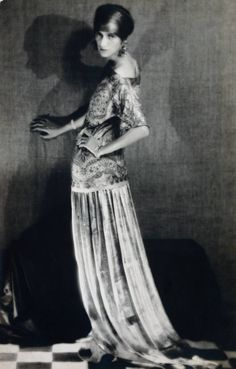 Peggy Guggenheim (1898-1979) She was a central figure in the Paris art world from 1922 onwards. The experimental artist Man Ray - another American abroad member of Guggenheim's circle; took a series of photographs of her in 1924. This portrait of her, wearing an extravagant gown and head-dress, clearly reveals her as an artistic trend-setter. The aesthetic quality of the photo itself is heightened by the dark shadows on the wall.