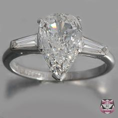 Engagement ring--pear cut center stone set between baguette diamonds.