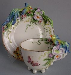 """Tea pair hand sculpting and painting, decorated with miniature paradise birds bright turquoise color. The composition is complemented delicate flowers orchids and small flowers. Flitting around the serene spotted butterflies. The work is done in mixed media - the molding of the white and colored porcelain masses, underglaze and overglaze painting, painted in gold and luster. Proceedings of the best firms in England and Germany, porcelain grade """"Parian""""."""