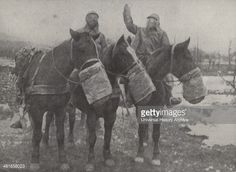 French cavalry soldiers with horses, stopped by a sentry with a warning: Attention, gas cloud, ahead. This column carrying ammunition to the front line, halts as each soldier prepares his gas mask. France, Western Front, World War One 1916