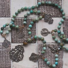 religious charms necklace on african turquoise beads. Layer it or wear alone. Love this but makes me think someone else would, too! -C!