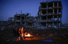Kurdish men sit near a bonfire near a destroyed building, in the Syrian Kurdish town of Kobane on March 22, 2015.