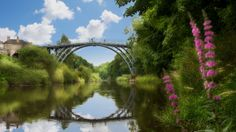 A photograph by photographer Niall O Cleirigh of the iron bridge in England with reflection and flowers and white fluffy clouds www. The Iron Bridge, Reflection, England, Clouds, Flowers, Photography, Play, Photograph, Fotografie