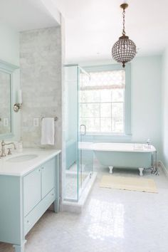 Who needs all-white when a baby blue bathroom can be just as soothing. Plus, white tiles and a hanging pendant light give the room glamour. Design by Mona Ross Berman.