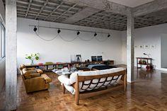 Eclectic industrial loft. Lush timber flooring, stark walls, industrial exposed beams, vintage furniture.