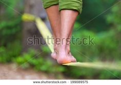 Slacklining is a practice in balance that typically uses nylon or polyester webbing tensioned between two anchor points. - Shutterstock Premier
