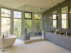 With natural stone walls, unobstructed views through floor-to-ceiling windows, a steam shower for two and a tub carved from limestone, this master bathroom is the perfect spa-like experience!!