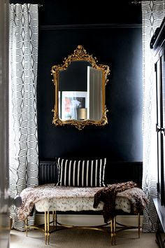 black bedroom with ornate gold mirror and gold bench