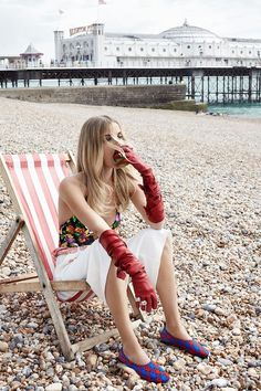 Denisa poses on the beach in long red gloves, a floral print shirt and white skirt