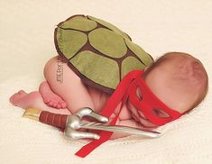 Another baby is dressed as a Ninja Turtle, with a costume complete with a shell and inflat...