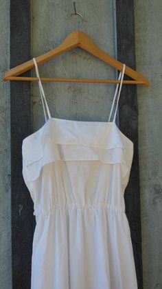 Lovely white cotton summer dress, 1980s vintage...  Cool and breezy, light and airy, ultra feminine....the perfect summer staple! Features a high cinched waist to show off your curves, spaghetti straps, a layer of ruffles at the collar and tiers at the hem, tiny string belt loops,