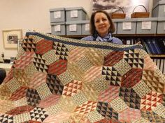 Mary Madden, director of the museum and education division at the Kansas Historical Society, holds an Ocean Waves patterned quilt made by Kansas pioneer Eliza Hobart Austin. The quilt was made in 1880 of fabric typically used for shirts.  PHOTOGRAPHS BY JAN BILES/THE CAPITAL-JOURNAL