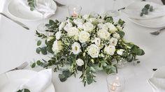 Vakker rundt borddekorasjon i hvitt og grønt.
