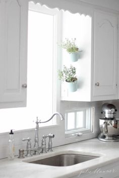 """Angling pots over the sink makes use of ample kitchen window light (and the """"short wall"""" on the side of a cabinet). Hanging herb garden as seen on House Beautiful Magazine"""