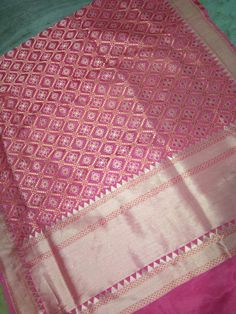 This onion pink saree with its closely woven geometric flowers in a lattice is framed by a zari border edged with a ribbon of pink. A plain pink blouse completes this handwoven Banarasi.
