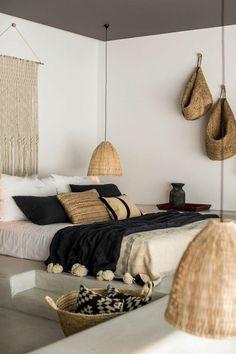 Chambre nature et zen très moderne. Lit bas lampes suspendues paniers et plaids. Coloris noirs blanc et beige.