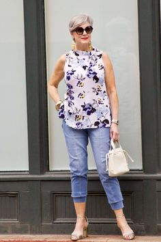 beth from Style at a Certain Age wears a floral top, denim joggers, gold metallic block sandals, and carries a drawstring crossbody handbag. Walmart we dress America Over 60 Fashion, Over 50 Womens Fashion, Fashion Over 50, Stylish Outfits For Women Over 50, Clothes For Women, Denim Joggers, Looks Chic, Denim Top, Ideias Fashion